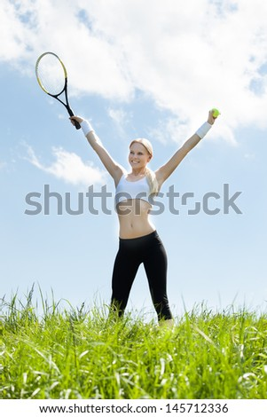 Female Tennis Player Standing In Field Holding Racquet And Ball - stock photo
