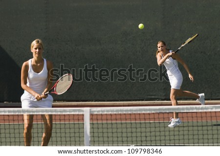 Female tennis player standing with her partner hitting shot in background - stock photo