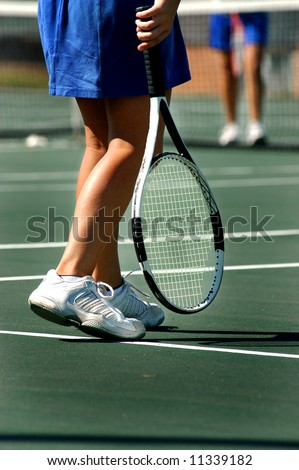 Female tennis player waits for game to begin.  Tennis racket hangs besides her feet.  Green court. - stock photo