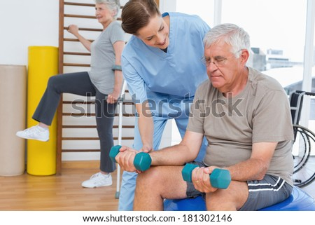 Female therapist assisting senior man with dumbbells in the medical office - stock photo