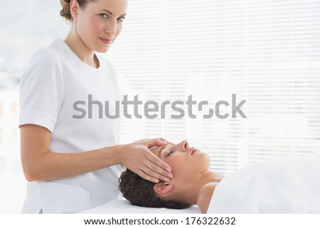 Female therapist giving head massage to woman in spa - stock photo