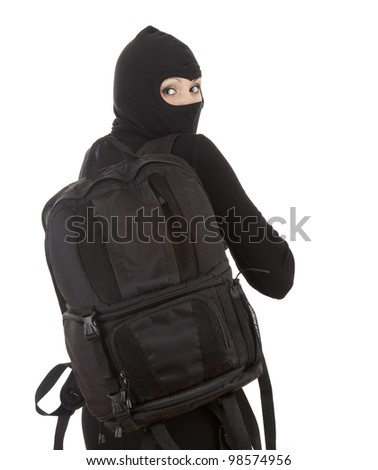 female thief in black balaclava with stolen backpack - stock photo