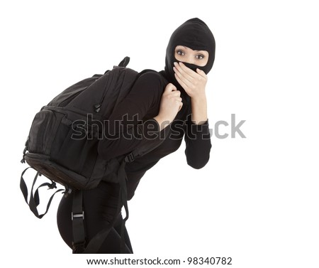 female thief in black balaclava with stolen rucksack - stock photo