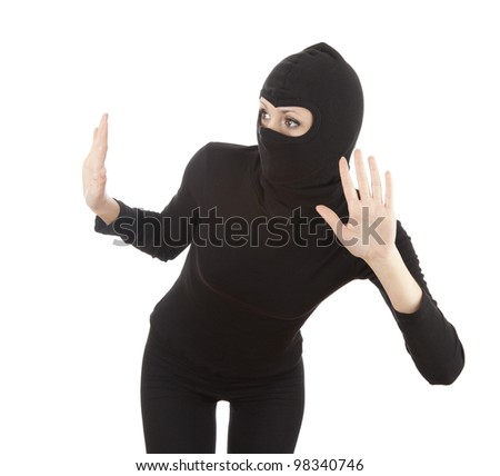 female thief in black clothes looking through the window, white background - stock photo