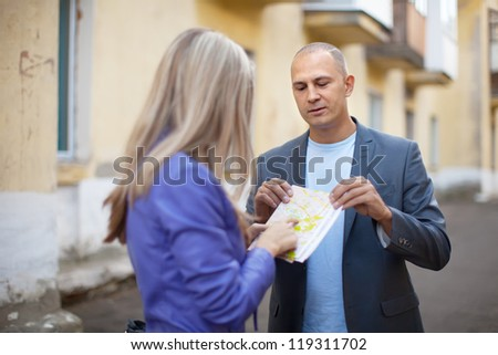 Female tourist asks for directions from man at old city street - stock photo
