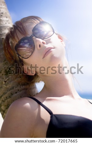 Female Tourist On Holiday Resting Against A Tropical Island Palm Tree On A Summer Beach In A Serene Portrait Of Peaceful Calm When Living A Traveling Lifestyle - stock photo