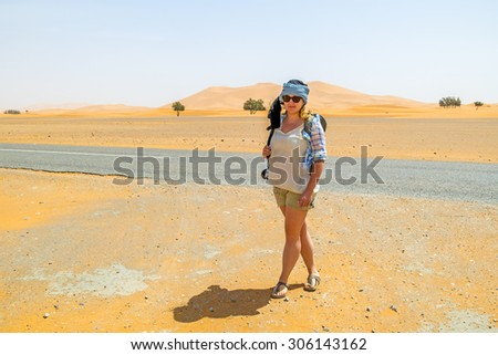 Female tourist on sand dunes in Merzouga, Morocco