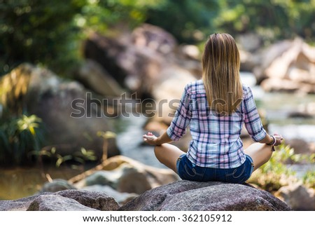 Female tourist sitting on the rock in meditation pose enjoying river view, peace of mind concept