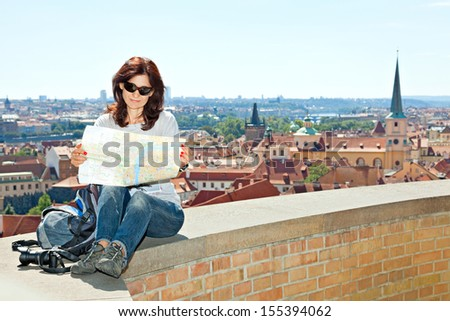 female tourist studying a map. Against the background of the Prague castle - stock photo