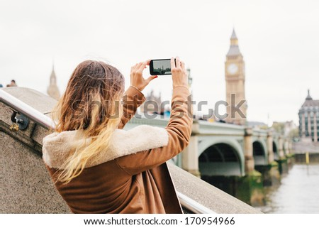 Female tourist taking a photo with mobile phone - stock photo