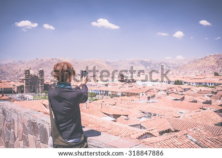 Female tourist taking selfie while visiting Inca's former capital Cusco, major travel destination in Cusco region, Peru. Marsala toned image, old retro cross processing, vignetting added. - stock photo