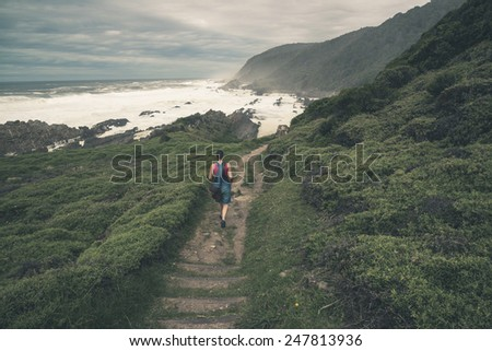 Female tourist walking on trail along the wild coast of Tsitsikamma National Park. Eastern Cape. South Africa. - stock photo