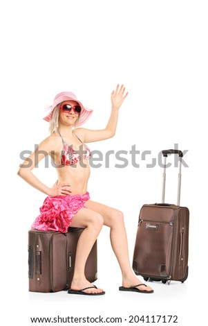 Female tourist waving with her hand seated on her luggage isolated on white background