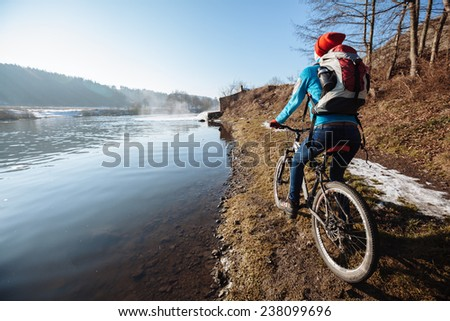 Female tourist with backpack and bicycle enjoying river view