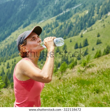 Female trail runner drinking water and having a break - stock photo