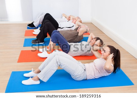 Female trainer and senior customers doing sit ups on exercise mats at gym - stock photo