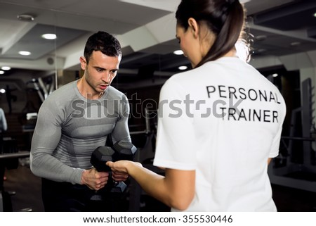 Female trainer doing workout with her client at gym - stock photo