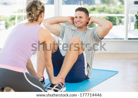 Female trainer helping fit man in doing sits up at gym - stock photo