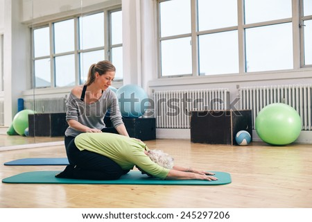 Female trainer helping senior woman doing yoga. Elder woman bending over a exercise mat with personal instructor helping at gym. - stock photo