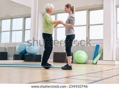 Female trainer helping senior woman standing on a balance board at gym. Elder woman exercising being assisted by personal trainer. - stock photo