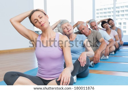 Female trainer with class stretching neck in row at yoga class