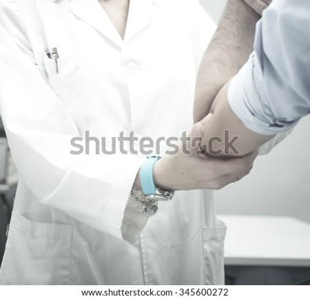 Female Traumatologist orthopedic surgeon doctor examining middle aged man patient to determine injury, pain, mobility and to diagnose medical treatment in shoulder, arm, elbow, wrist and fingers. - stock photo