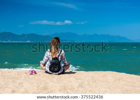 Female traveler on the beach enjoying sea view - stock photo