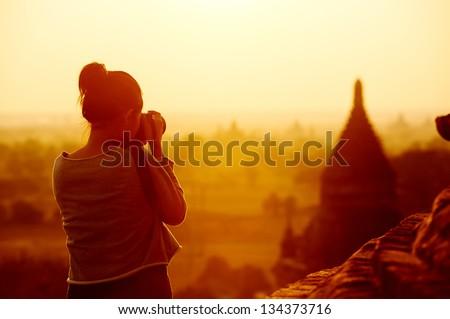female traveler photographing temples at Bagan Myanmar Asia at sunrise - stock photo