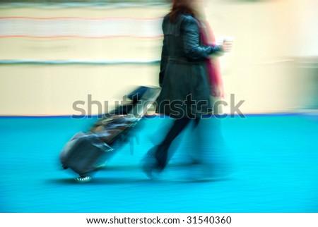 Female traveler rushing through an airport terminal - stock photo