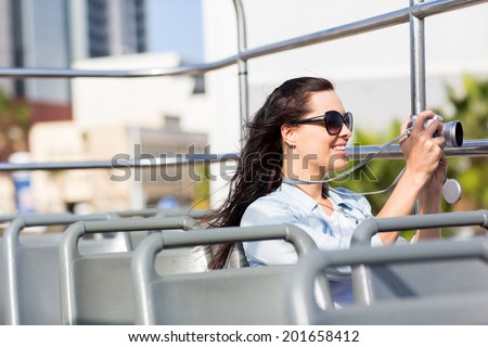 female traveller taking video of the city using digital camera from an open top bus - stock photo