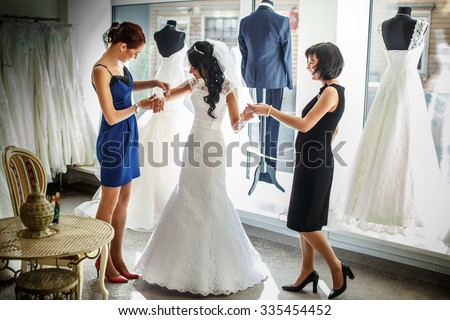 Female trying on wedding dress in a shop with two women assistants. - stock photo