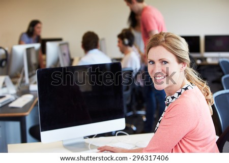 Female Tutor Using Computer In IT Class - stock photo