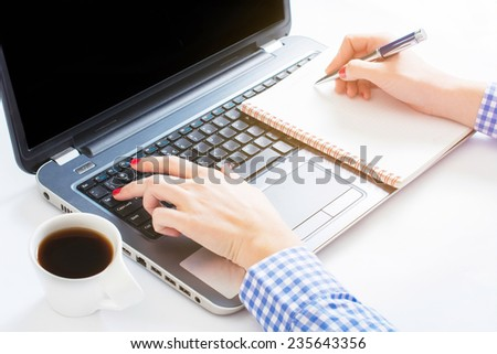 Female typing on laptop keyboard and writing on blank paper,selective focus - stock photo