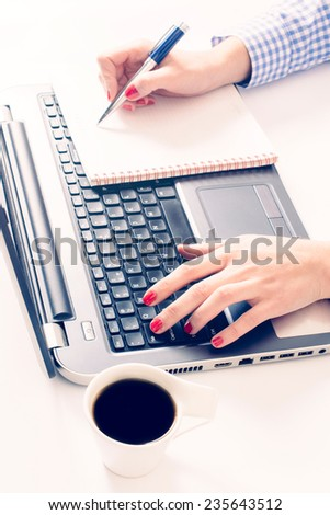 Female typing on laptop keyboard and writing on blank paper,selective focus