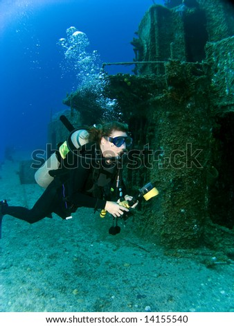 Female Underwater Photographer swimming off the side of a sunken Destroyer
