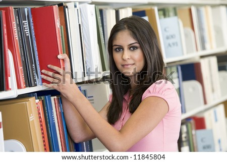 Female university student selecting book from shelf
