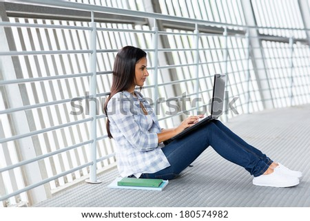 female university student sitting on the floor working on laptop computer - stock photo
