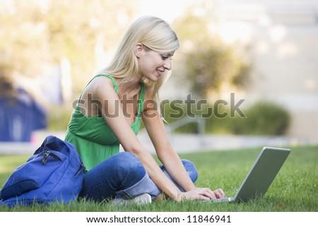 Female university student using laptop outside - stock photo