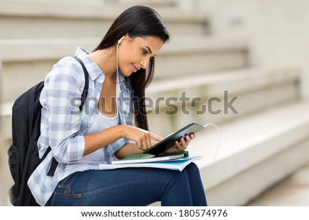 female university student using tablet computer listening music on campus - stock photo