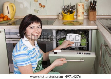 Female using dishwashing machine. Attractive brunette woman cleaning kitchen. - stock photo
