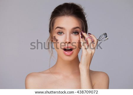 Female using eyelash curler