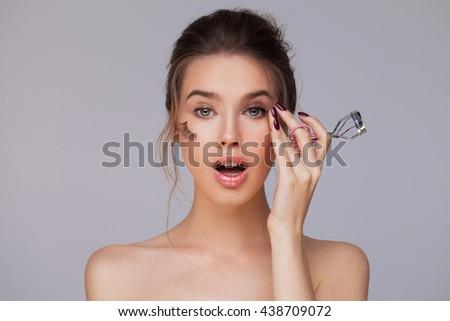 Female using eyelash curler - stock photo