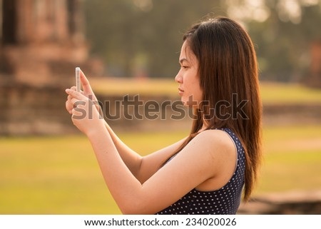 female using smartphone taking a photo at sight seeing place  in Thailand ancient temple - stock photo