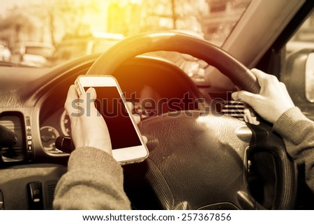 Female using smartphone while driving car. Vintage filter. - stock photo
