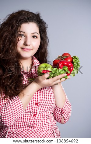 Female vegetarian with vegetables on the background