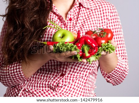 Female vegetarian with vegetables on the background - stock photo