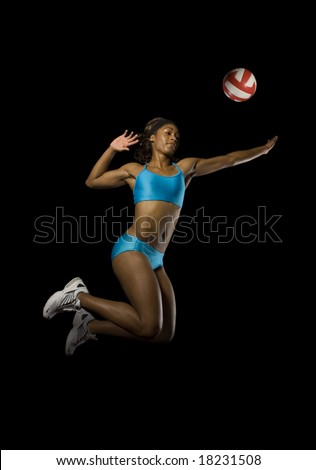 Female volleyball player in mid air for spike - stock photo