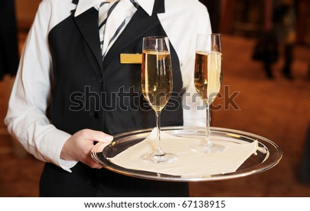 Female waiter welcomes guests with sparkling wine - stock photo