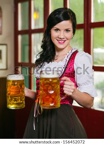 female waitress wearing traditional dirndl and holding huge beers in a pub. - stock photo