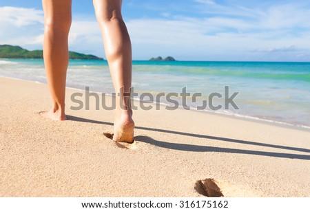 Female walking on a beautiful white sand beach. (location Hawaii) - stock photo